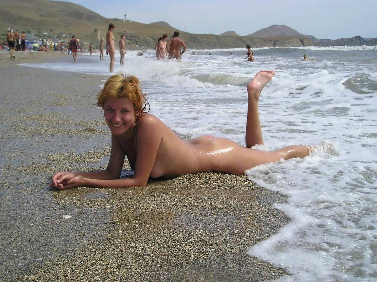 Happy naked girl letting her body washed by sea