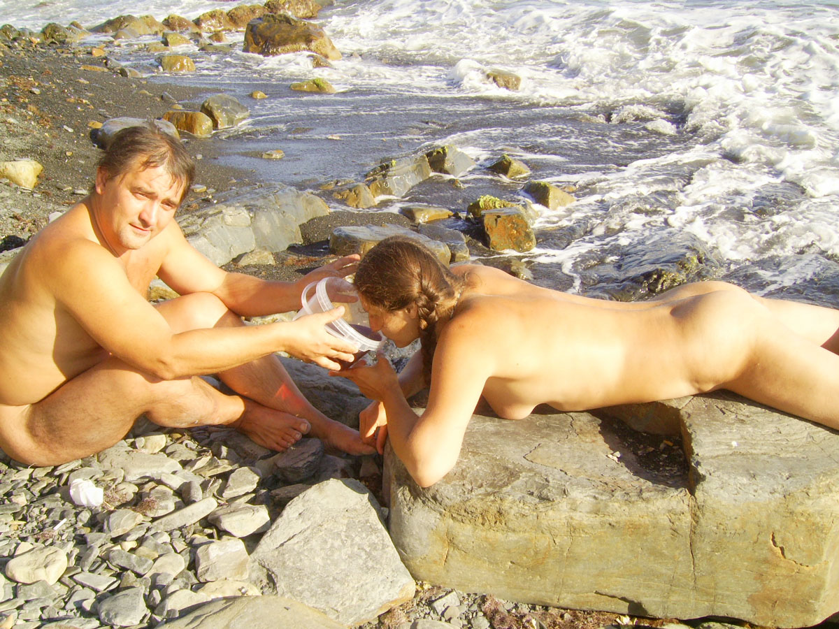 Nudist couple on a rocky shore