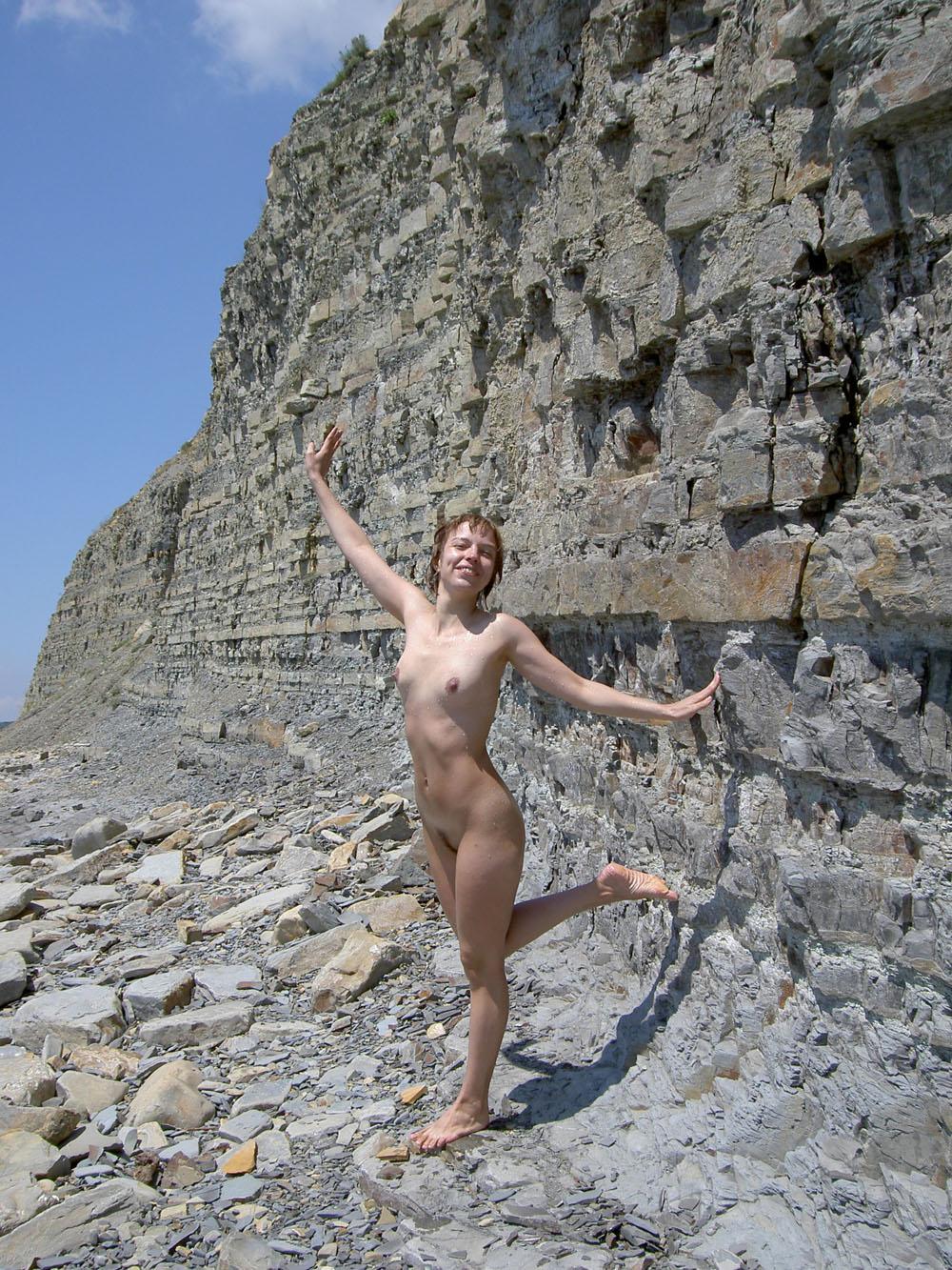 Nude happy girl near a wall of rocks