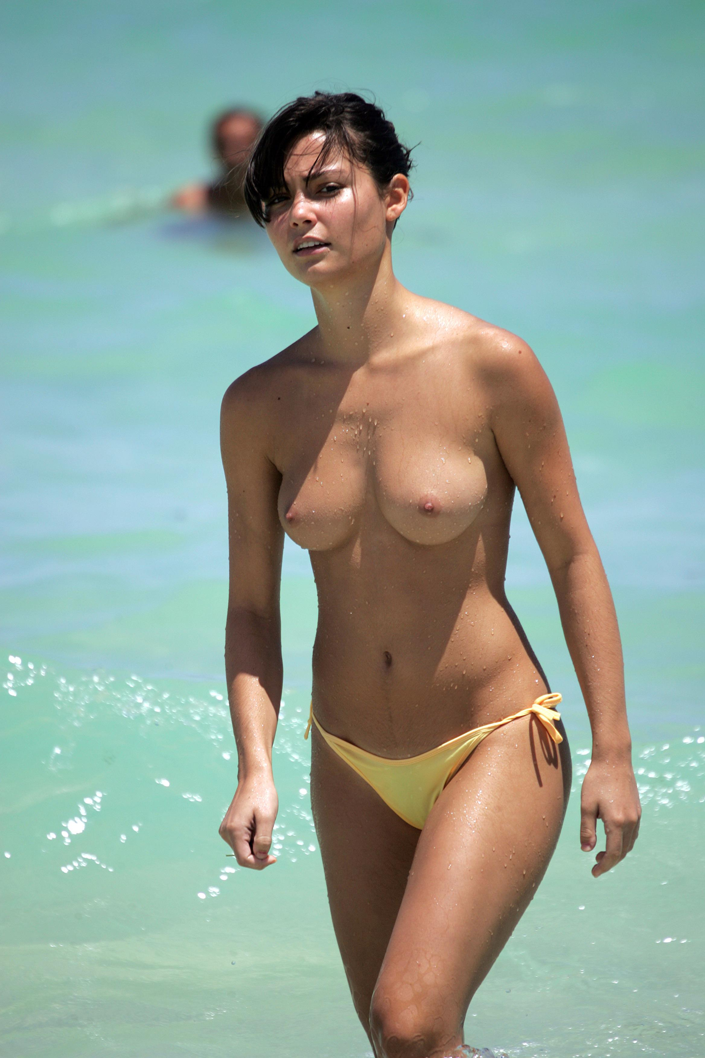 Smokin hot brunette enjoying the ocean while topless