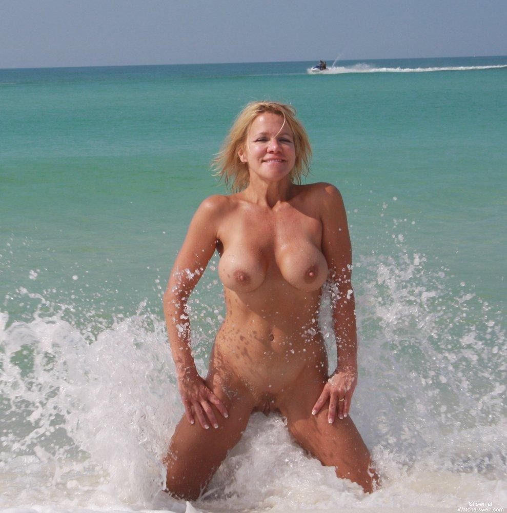 Flirty blonde splashing nude in the surf