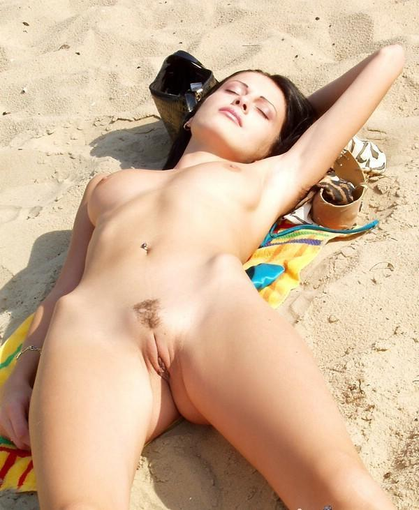 Foxy babe napping fully nude on the beach