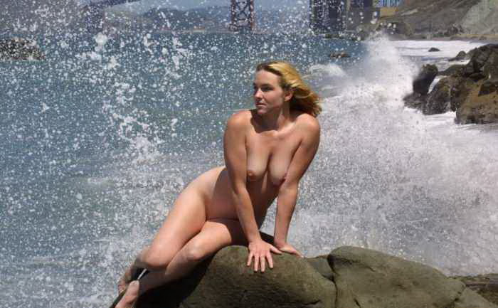 Nude nymph on a rocky shore and splashing waves