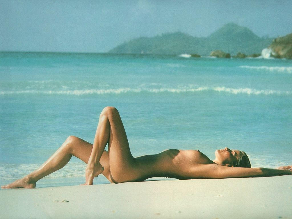 Nudist beauty laying naked on the warm sands