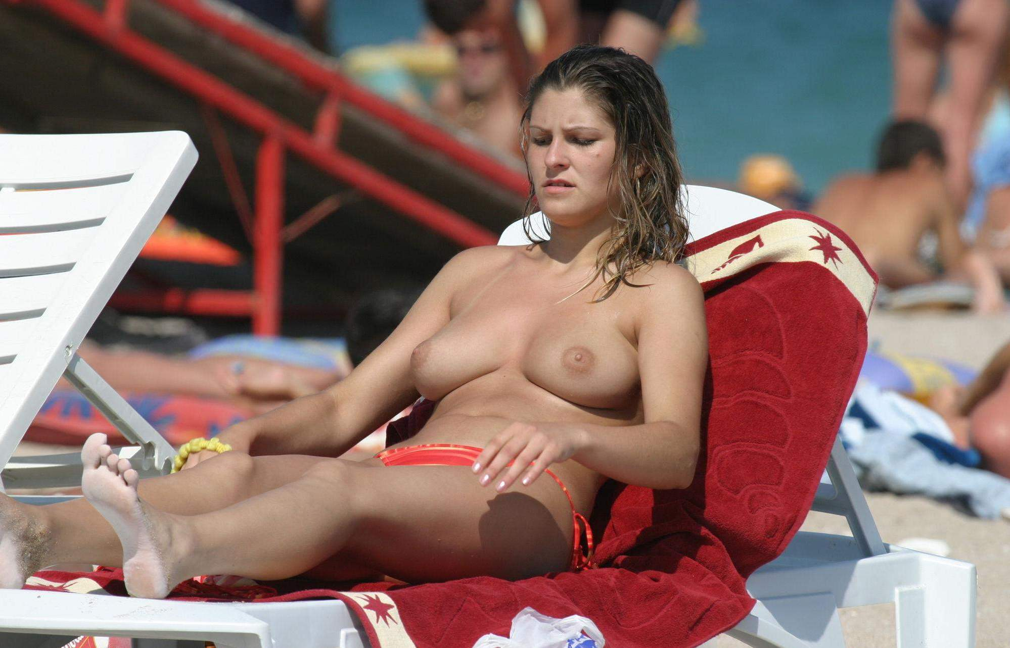 Topless girl enjoying the sunny beach