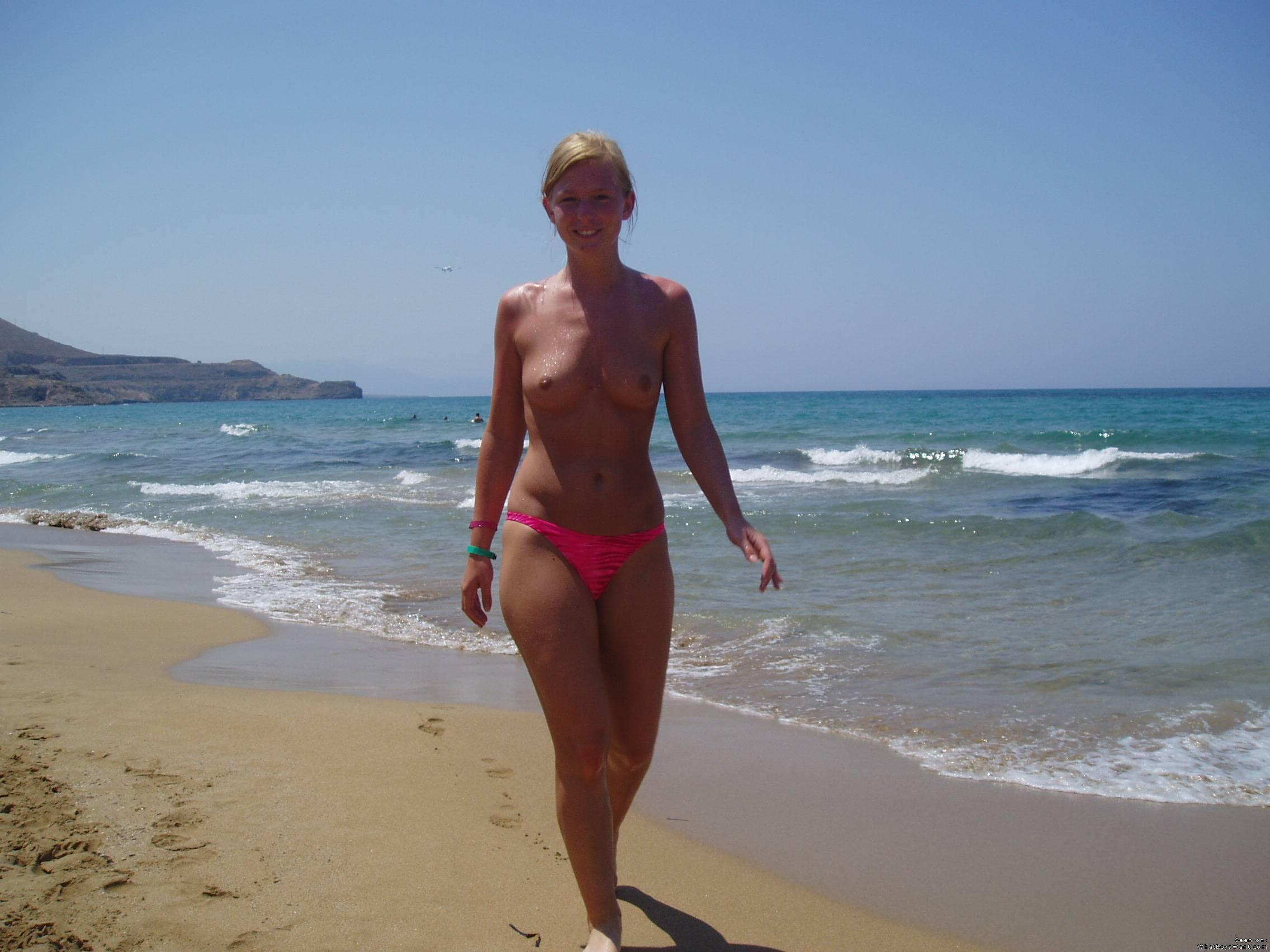 Topless pretty girl walking on the beach in her pink bikinis